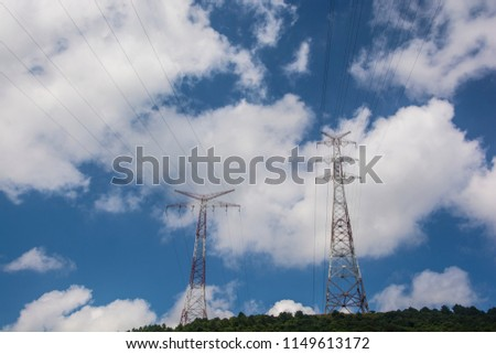 Cloudy Sky and Electricity Transmission Towers on a Forest Hill #1149613172