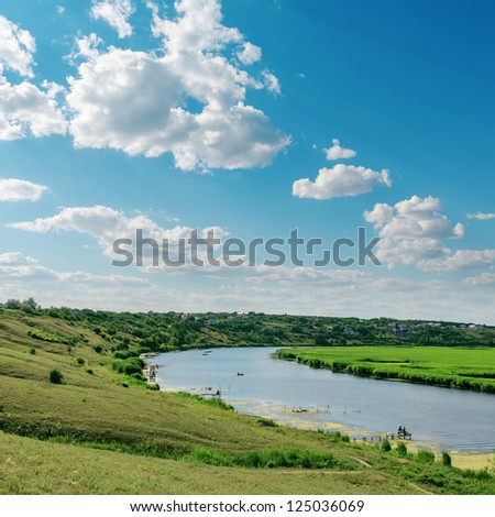 cloudy sky and river in green landscape