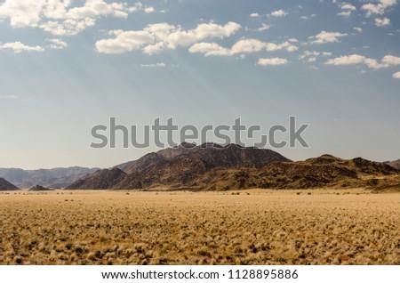 Cloudy sky and sun rays at Tiras Mountains