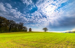 Cloudy sky over a green agriculture meadow. Agriculture field above cloudy sky. Cloudy sky over agriculture field