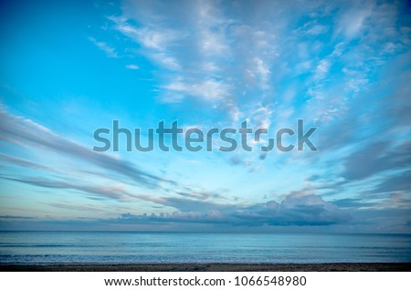 Cloudy sky over the sea in the evening light #1066548980