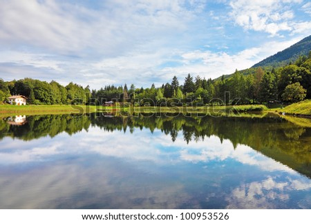 Cloudy sky reflected in water, a small lake in the mountains of northern Italy. - stock photo