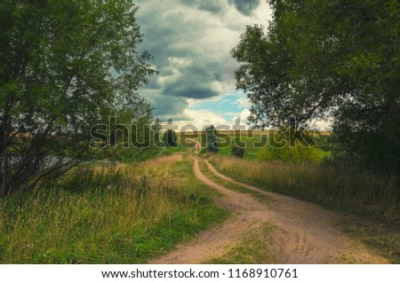 Cloudy summer landscape with ground country road.Dark stormy clouds in dramatic overcast sky.Fields,green meadows and woods.Tula region,Russia.