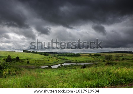 Cloudy summer landscape with small river.Dark stormy clouds in dramatic overcast sky.Fields,green meadows and woods.Rainy season.