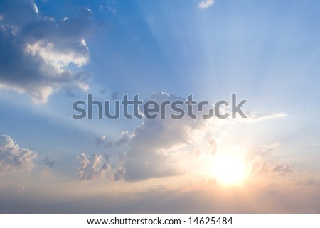 cloudy sunrise with sunbeams and blue sky - stock photo