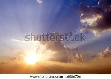 cloudy sunrise with sunbeams and blue sky