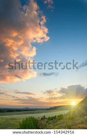Cloudy sunset in a wheat field with a beautiful red clouds #154342916
