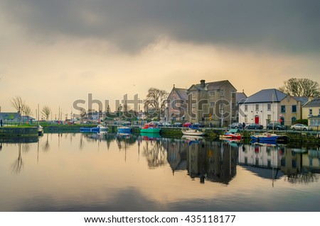 Cloudy sunset over the Galway Dock, with fishing boats and Dominican church. Water reflection.