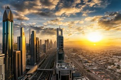 Cloudy sunset over the modern skyline of Dubai, UAE,  with reflections in the diverse skyscrapers and buildings