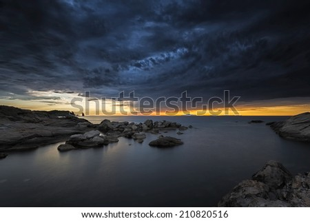cloudy sunset over the sea in a rocky beach with stones and red dusk. epic sky