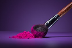 Clouse-up of makeup brush and face powder on purple background