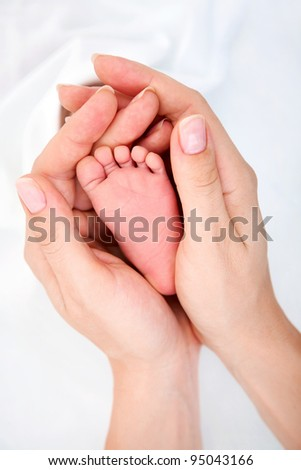 Clouse-up of newborn baby's foot in mammy's hands