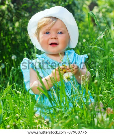 Clouse-up portrait pretty little girl sitting in the grass in the park