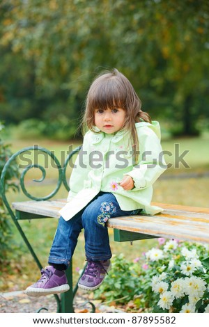 Clouse-up portrait pretty little girl sitting on a bench in the park