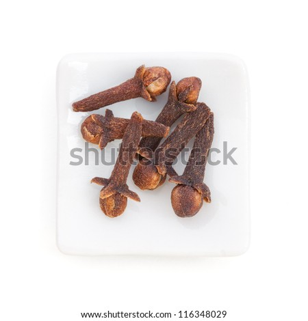 Clove (Syzygium aromaticum) in a white bowl on white background. Used as a spice in cuisines all over the world. The plant is also used in medicine.
