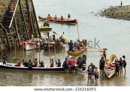 CLOVELLY, UNITED KINGDOM - AUGUST 16  rowing boats teams descend from boat on sand at harbor during Copilot Gigs Regatta rowing competition, shot on 2014 august 16, Clovelly, Devon, United Kingdom
