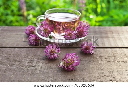 Clover flower tea in the glass cups on a wooden table #703320604