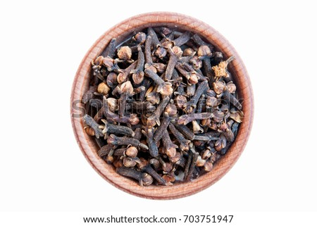 Cloves. Cloves is isolated on a white background. Clove in a wooden bowl  #703751947