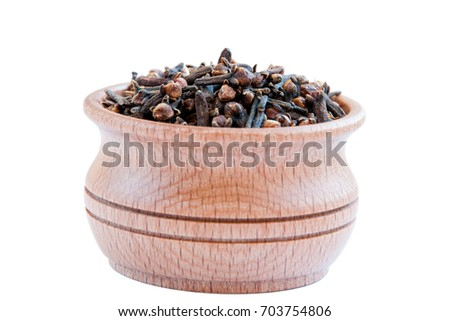 Cloves. Cloves is isolated on a white background. Clove in a wooden bowl  #703754806