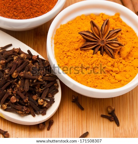 Cloves, paprika and turmeric powder in white bowls with anise flower on top, on wooden table background