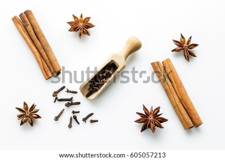 cloves with wooden spoon and cinanmon and star anise on white background #605057213