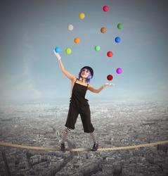 Clown as juggler is balancing on rope