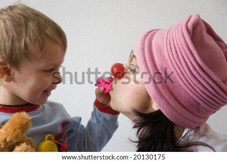 Clown-doctor : boy is playing with red nose clown and his choo-choo train toy.