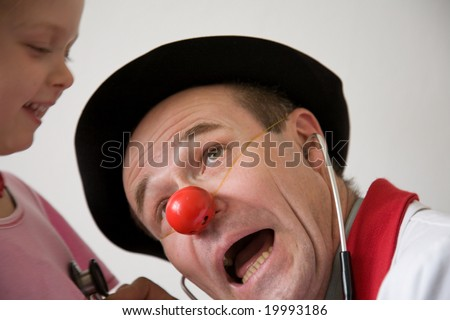 Clown-doctor : girl and clown with red nose are smiling and joking during medical examination.
