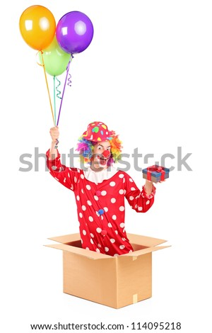 Clown holding balloons and a gift in a cardboard box, isolated on white background