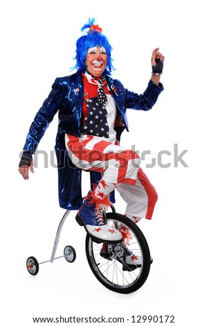 Clown riding a unicycle with training wheels - stock photo