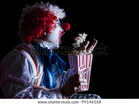 clown throwing popcorn into his mouth while watching a movie