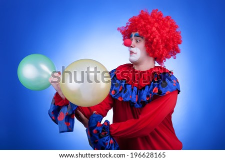 Clown with two balloons in hand on blue background. Studio professional lighting