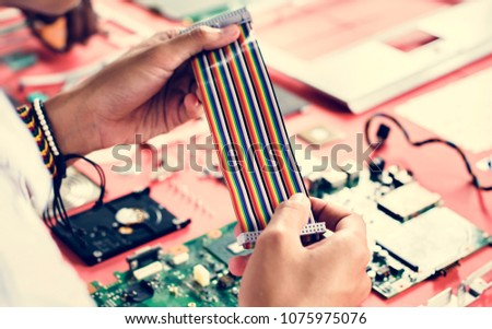 Clsoeup of hands holding computer breadboard flat wires cables  #1075975076
