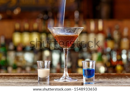 Photo of Club cocktail lamborghini. Burning drink on the basis of sambuka and liqueurs, space for text, photo for the menu.