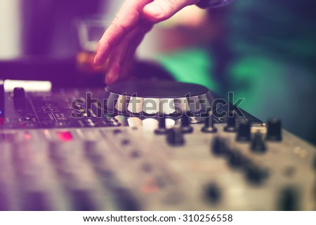 Stock Photo Club DJ playing mixing music on vinyl turntable at party