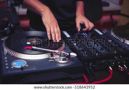 Club dj plays music at hip hop party.Turntable vinyl player for disc jockey to scratch records,mix tracks.Music festival performance.Disc jockey scratches vinyls on turntables on stage in nightclub