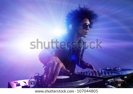 Club DJ with afro hairstyle playing mixing music on vinyl turntable at party wearing sunglasses with lens flare from nightlife lights.