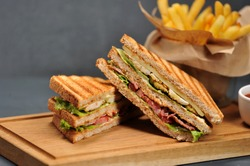 Club sandwich on a wooden board. Next to French fries and a cup of ketchup sauce. The filling of the sandwich consists of chicken breast, bacon, cheese, lettuce, tomato. Close-up. Macro photography.