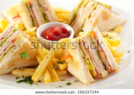 Club Sandwich with Cheese, Pickled Cucumber, Tomato and Smoked Meat. Garnished with French Fries