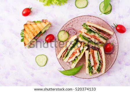 Club sandwich with chicken breast, bacon, tomato, cucumber and herbs. Top view/