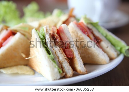 Club sandwich with coffee on wood background
