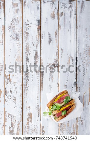 Club sandwich with steak and halloumi cheese served with mustard ruccola and parsley over a wooden serving board #748741540