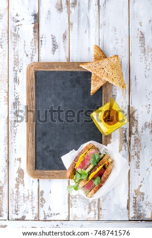 Club sandwich with steak and halloumi cheese served with mustard ruccola and parsley over a wooden serving board #748741576