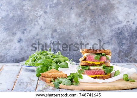 Club sandwich with steak and halloumi cheese served with mustard ruccola and parsley over a wooden serving board #748741645