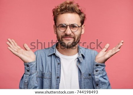Clueless doubtful displeased male with attractive appearance shrug shoulders in uncertainty, hesitates whether go on party or date with girlfriend. Hesitant man doesn`t know how change future life