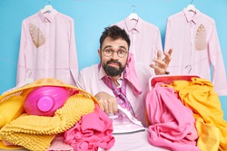 Clueless hesitant bearded man poses against laundry baskets has sock on ear shrugs shoulders doesnt know from what to begin busy doing ironing at home poses in dressing room against blue wall