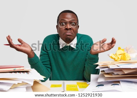Clueless puzzled dark skinned man shruggs shoulders, feels confused as cant finish task, wears elegant green jumper, doesnt know from what to start, busy with writing diploma paper, uses documents