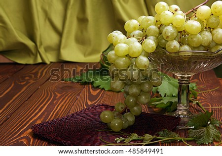 Cluster of grapes in vase for fruits over on wooden table against background cloth olive color #485849491
