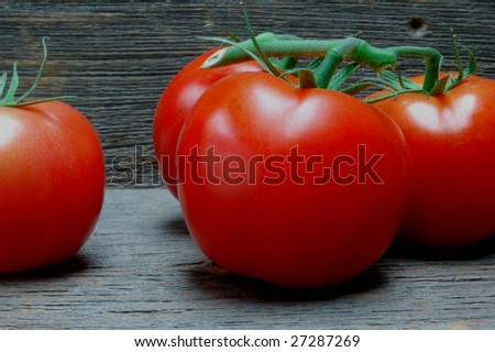 Cluster of red vine tomatoes on old barn wood planks