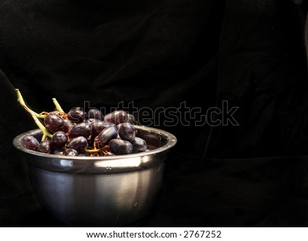 Clusters of red grapes in a stainless steel bowl on a black velvet background.